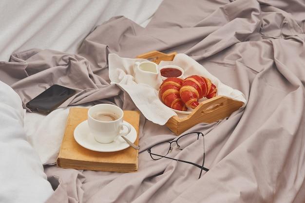 Ontbijt op een verfrommeld bed, koffie, croissants, boek, gsm