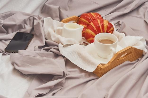 Ontbijt op een verfrommeld bed, koffie, croissants, mobiele telefoon