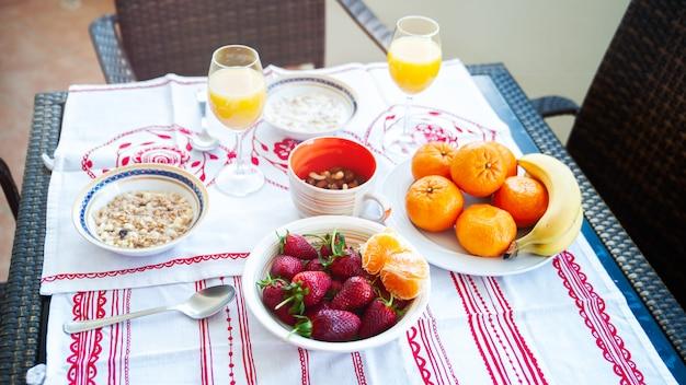Ontbijt op tafel, sap, ontbijtgranen en fruit in de zon. goed eten, goed ontbijt, aardbeien, mandarijnen, bananen, noten