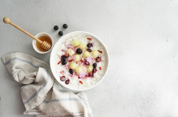 Ontbijt rijst porrige met honing en meloen, bessen