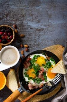 Ontbijt roerei met spek koffie bessen koekjes noten en sap bovenaanzicht