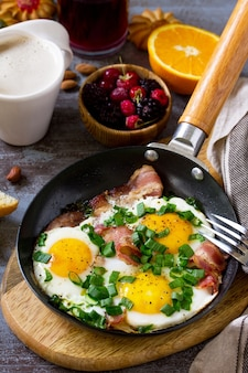 Ontbijt roerei met spek koffie bessen koekjes noten en sap op donkere tafel oppervlak