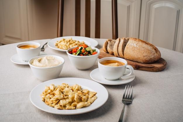 Ontbijt. roerei of omelet, hummus, koffie, groentesalade, brood. eettafel