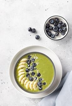 Ontbijt smoothie kom met groene matcha, banaan, bosbessen. veganistisch eten