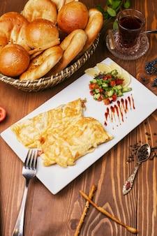 Ontbijt-snack-pannenkoeken, omeletten met plantaardige salade en broodjes in witte plaat