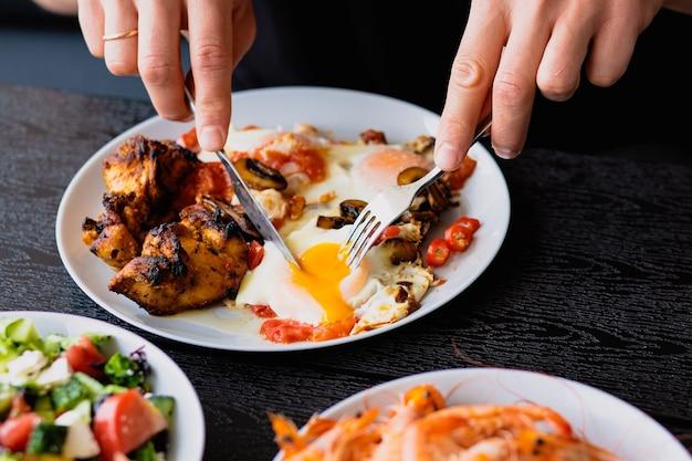 Ontbijt snijdt gebakken eieren smeren dooier voor ontbijt lunch op het terras de man eet
