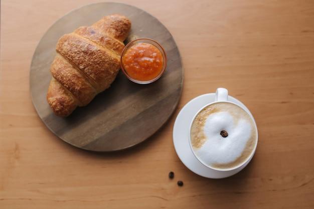 Ontbijt thuis. cappuccino met lege croissants. ochtend met koffie. abrikozenjam op plaat. bovenaanzicht