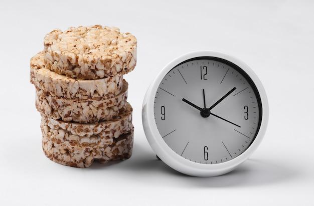 Ontbijt tijd. dieet concept. stapel volkoren knapperig brood en klok op wit oppervlak
