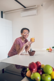 Ontbijt tijd. donkere schattige jonge vrouw die een gezond ontbijt heeft