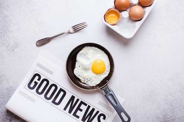 Ontbijt tijd. gebakken eieren in een pan met een wekker en een krant op een lichtgrijze tafel met een gestructureerde achtergrond.
