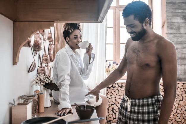 Ontbijt tijd. lachende afrikaanse amerikaan in geruite broek met fles melk over plaat en vrouw in shirt zittend op tafel koffie drinken