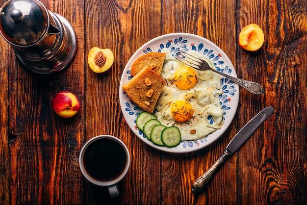 Ontbijt toast met gebakken eieren met groenten op plaat en kopje koffie met fruit over donkere houten, bovenaanzicht. gezond voedselconcept.