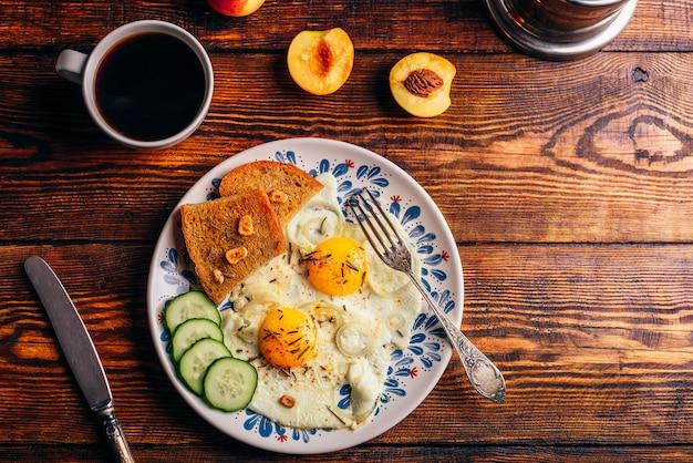 Ontbijt toast met gebakken eieren met groenten op plaat en kopje koffie met fruit over donkere houten tafel, bovenaanzicht. gezond voedselconcept.