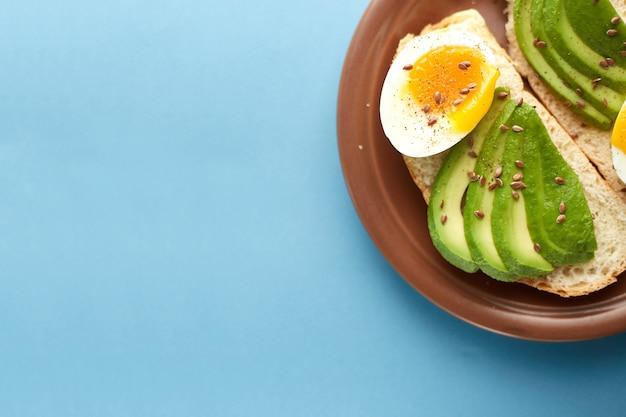 Ontbijt toast met gekookt ei en avocado op de witte plaat
