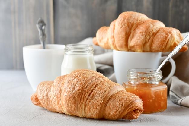 Ontbijt twee witte kopjes koffie met melk, twee croissants en appeljam in een glazen pot