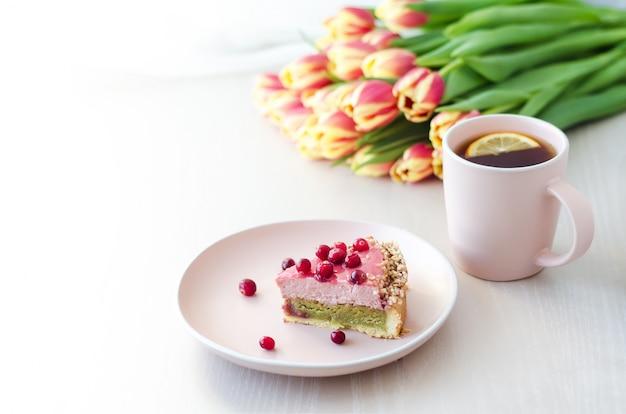 Ontbijt, vakantie, ochtend met bloemen tulpen, cake, thee, koffie in roze mok op lichte ondergrond
