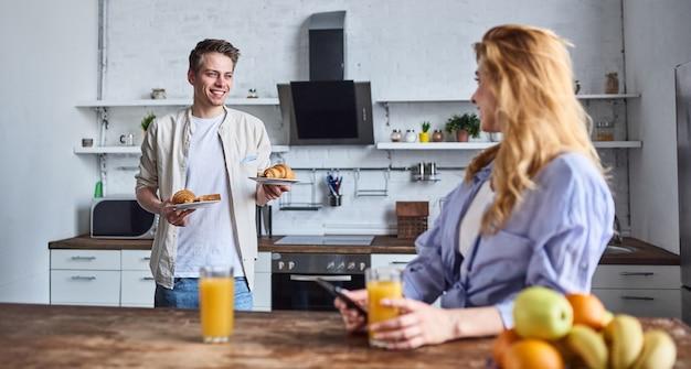 Ontbijt van een jong verliefd stel in de thuiskeuken. mooi meisje met een telefoon in haar hand drinkt sap. vriend maakte ontbijt klaar.