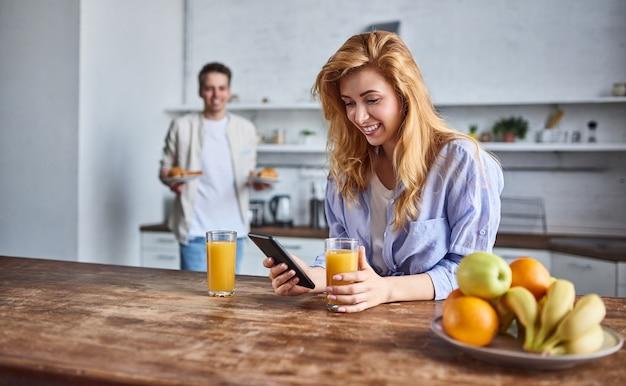 Ontbijt van een jong verliefd stel in de thuiskeuken. mooi meisje met een telefoon in haar hand drinkt sap.