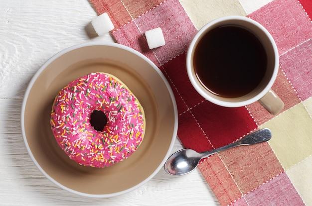 Ontbijt van een koffiekopje en roze donut op witte tafel met tafellaken, bovenaanzicht