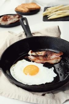 Ontbijt van eieren en gebakken spek in de pan