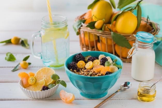 Ontbijt van muesli, fruit, vers geperst sap en thee op een witte tafel.