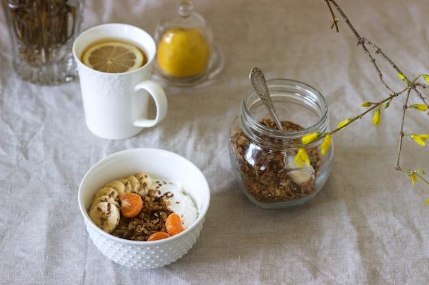 Ontbijt van muesli met yoghurt en thee en forsythia bloemen op een linnen tafellaken. rustieke stijl.
