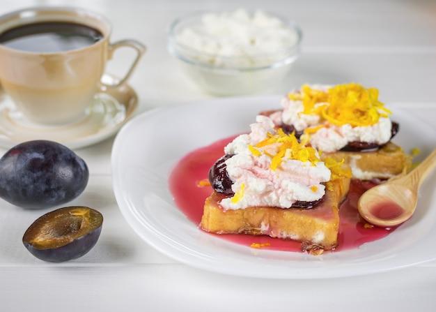 Ontbijt van stokbrood met kwark, pruimenjam en sinaasappelschil op een witte tafel.