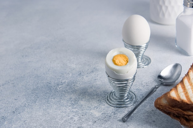 Ontbijt van twee hardgekookte eieren en toast op een lichte achtergrond met kopie ruimte.