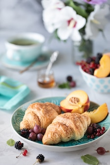 Ontbijt van verse bessen en fruit met croissants, thee een boeket van zomerbloemen.