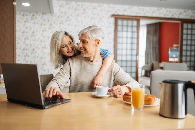 Ontbijt van vrolijk volwassen liefdepaar thuis. rijpe echtgenoot en vrouw bij laptop in de keuken, gelukkige familie