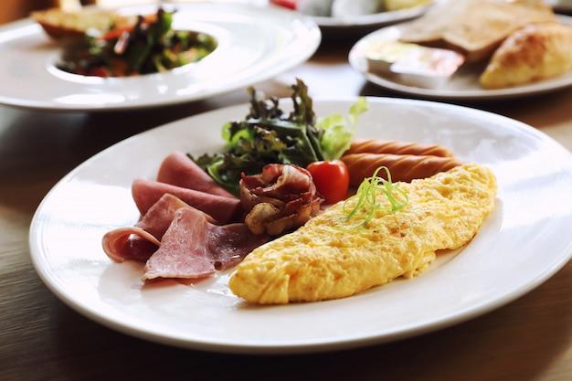 Ontbijt vastgestelde omelet met worstbacon en salade op hout