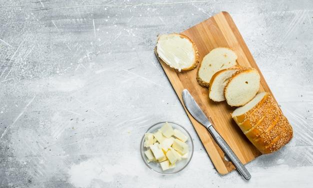 Ontbijt. vers brood en boter op een houten bord.