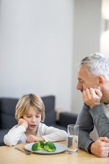 Ontbijt. volwassen man probeert zijn zoon gezond te laten eten terwijl de jongen er ongelukkig uitziet