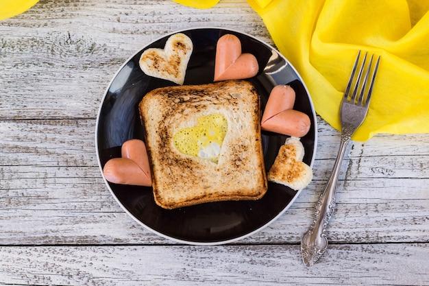 Ontbijt voor de viering van valentijnsdag - toast met roerei in de vorm van harten, worstjes in een bord en een vork