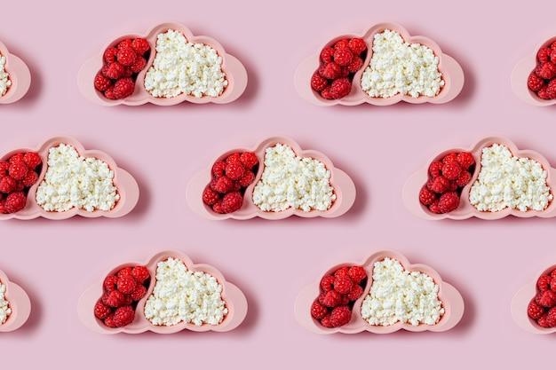 Ontbijt voor kinderen. bord in de vorm van een wolk met kwark en bes op roze achtergrond. eten idee voor kinderen.