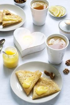 Ontbijt voor twee met pannenkoeken, citroenroom en thee. ontbijt op valentijnsdag.