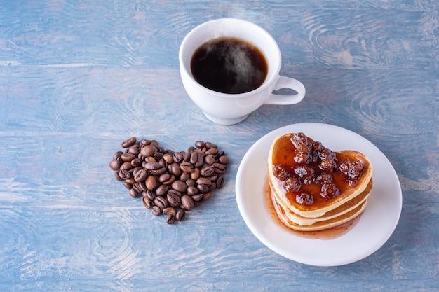 Ontbijt voor valentijnsdag. zelfgemaakte hartvormige pannenkoeken met bessenjam, hart bekleed met koffiebonen en een witte kop warme koffie op een blauwe houten tafel