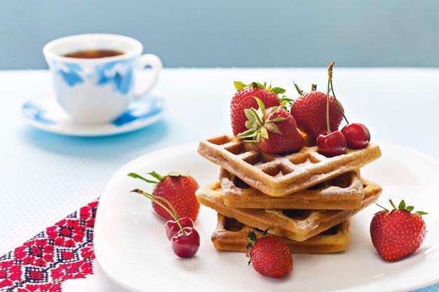 Ontbijt. weense wafels met aardbeien en kersen en koffie.