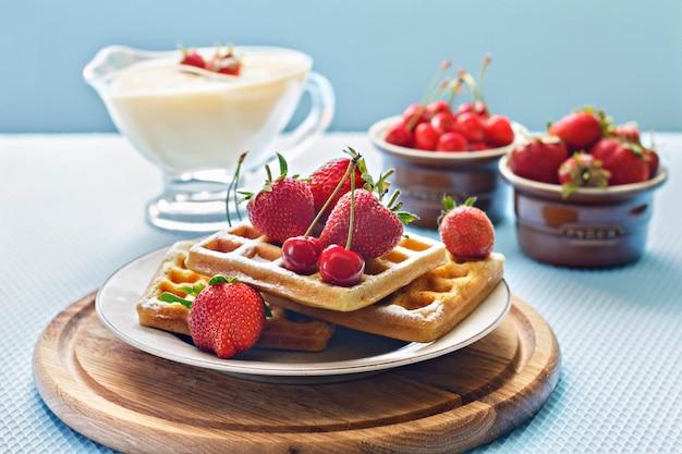 Ontbijt. weense wafels met aardbeien en kersen en room.