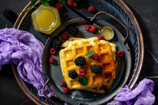 Ontbijt zelfgemaakte belgische wafels met bessen en honing op donkere tafel bovenaanzicht plat leggen