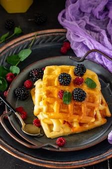 Ontbijt zelfgemaakte belgische wafels met bessen en honing op donkere tafel