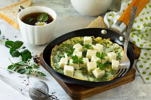 Ontbijtachtergrond gebakken eieren met spinazie-fetakaas op stenen tafel