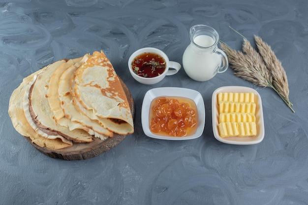 Ontbijtarrangement versierd met tarwe stengels op marmeren tafel.