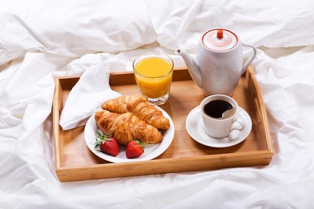 Ontbijtblad op bed, koffie, croissants, sap en verse aardbeien