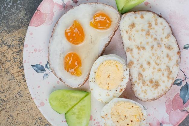 Ontbijtbord met brood en eieren op marmeren oppervlak.