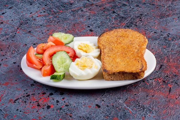 Ontbijtbord met eieren, komkommer en sneetjes brood.