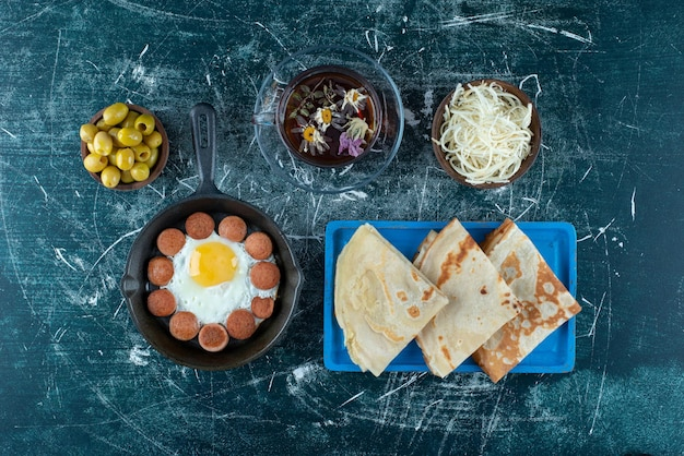 Ontbijtbord met gebakken eieren, worst en pannenkoeken.