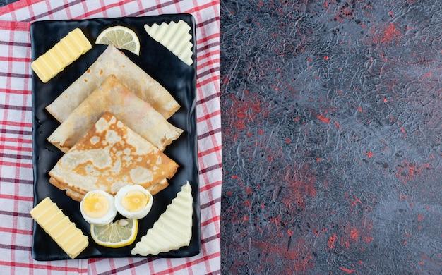 Ontbijtbord met pannenkoeken, kaas, citroen en eieren.