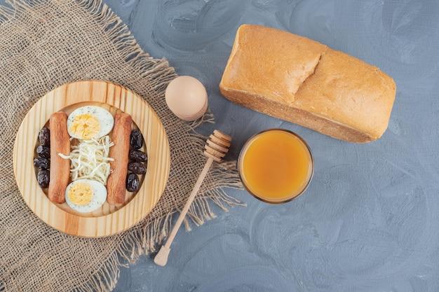 Ontbijtbord met sap en brood op marmeren tafel.