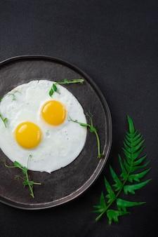Ontbijtbord met twee gebakken eieren, kruiden op zwarte achtergrond, close-up, bovenaanzicht, weergave van bovenaf, lay-out, plat leggen, kopie ruimte